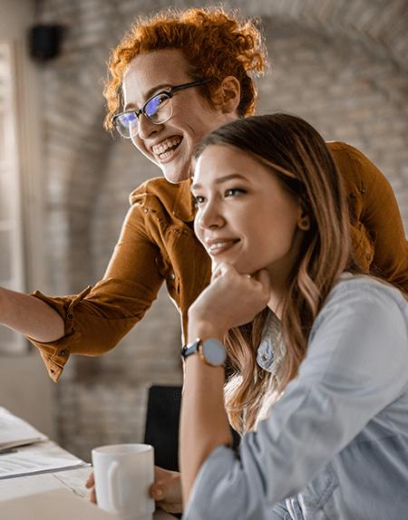 Szkolenia szyte na miarę, dwie koleżanki z pracy wpatrzone w ekran laptopa